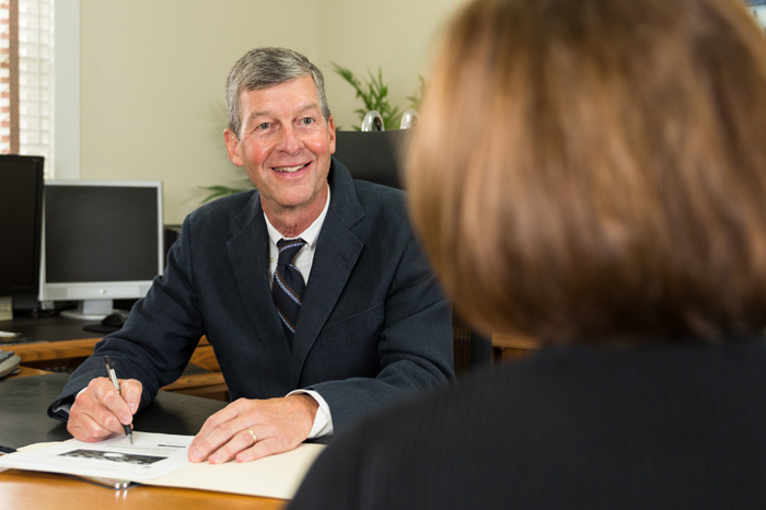 Man writes in a file while speaking with a client